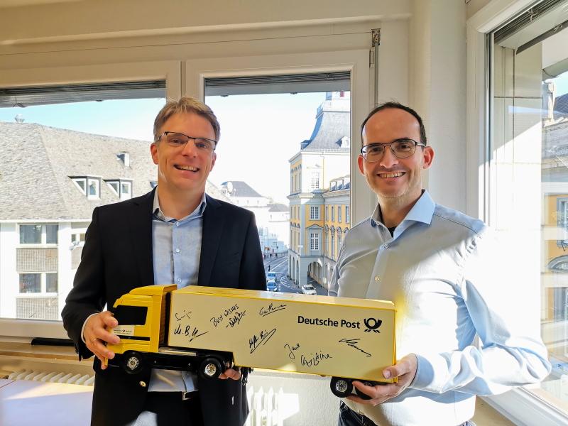 """CEO Martin Schulze und Managing Partner Martin Bernemann mit einem """"Deutsche Post DHL""""-Truck zum BusinessCode Jubiläum"""